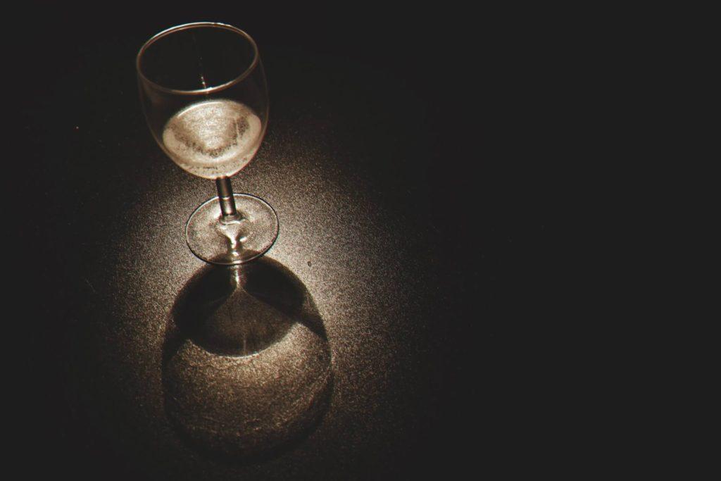 White wine glass under spotlight