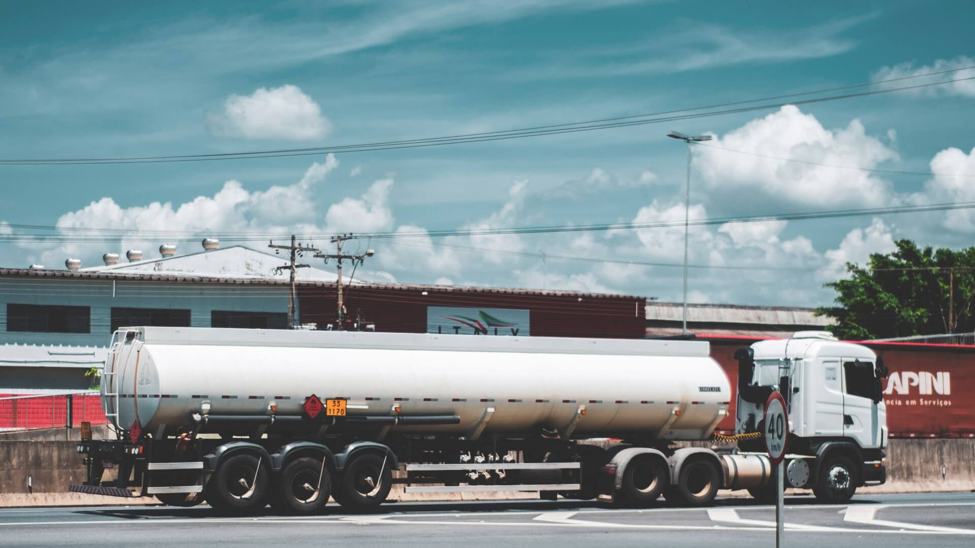 Tanker truck in front of businesses on a sunny day